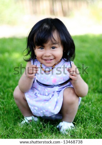 Smiling toddler girl playing with sunglasses on a grass