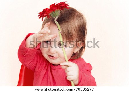 Smiling toddler on a pale background holding a red flower above her head.