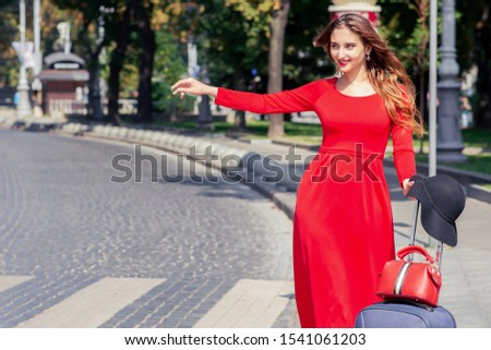 Smiling tourist girl in red dress with valise catches a taxi on street of city. Beautiful tourist woman is catching a taxi on road of city.