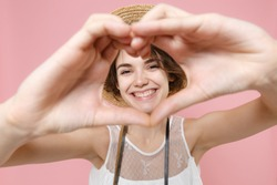 Smiling tourist woman in dress hat photo camera isolated on pink background. Traveling abroad to travel weekends getaway. Air flight journey concept. Showing shape heart with hands, heart-shape sign