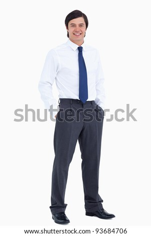 Smiling tradesman with his hands in his pockets against a white background