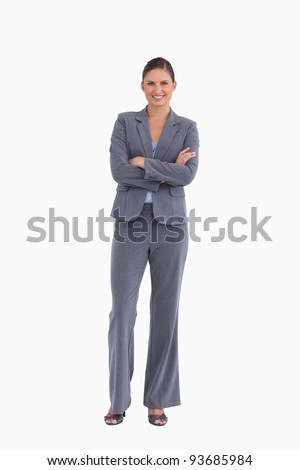 Smiling tradeswoman with her arms folded against a white background