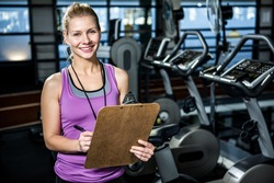 Smiling trainer holding clipboard at the gym