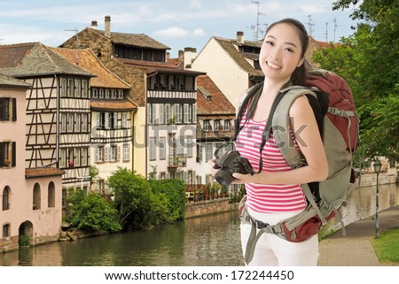 Smiling traveling Asian girl holding a camera and looking at you in the street of Europe.