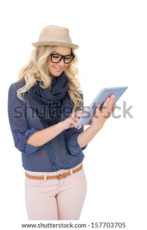 Smiling trendy blonde using tablet computer on white background