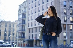 Smiling trendy dressed female tourist standing on promotional background satisfied with connection in roaming talking on mobile, attractive hipster girl in stylish wear having phone conversation