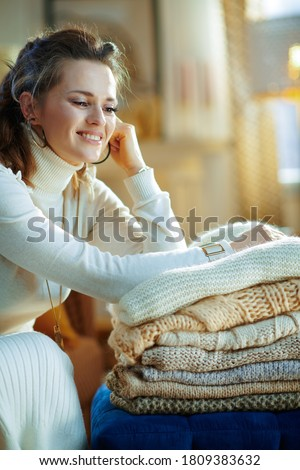 smiling trendy middle age woman in white sweater and skirt with pile of sweaters in the modern living room in sunny winter day.