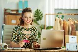 smiling trendy small business owner woman with credit card and laptop making online purchases on e-commerce website in the office.