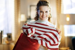 smiling trendy woman in white sweater and skirt with red shopping bag showing purchased sweater in the modern living room in sunny winter day.