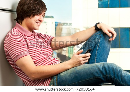 smiling trendy young guy typing a message on mobile phone - stock photo