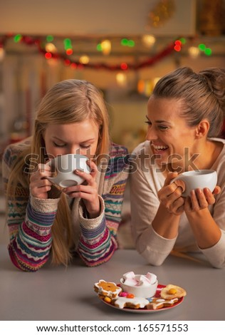 Smiling two girlfriends having christmas snacks in christmas decorated kitchen