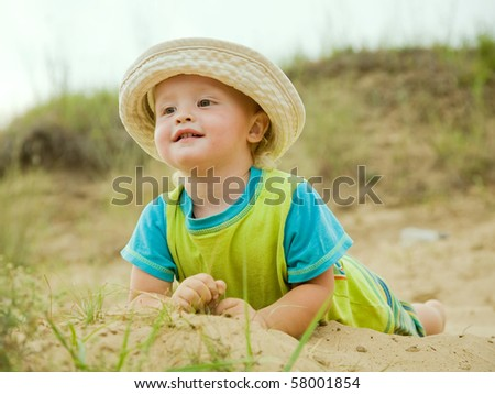 Smiling two-year boy in hat  at sand beach