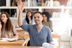Smiling university college student raising hand, asking question during class, attractive man sitting at desk in classroom with multinational diverse classmates group, education and knowledge