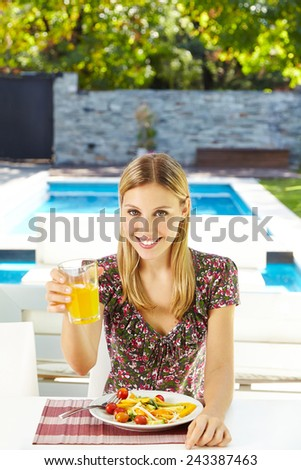 Smiling vegetarian woman eating salad with juice at lunch