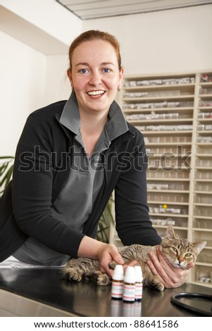smiling veterinarian looking into camera and holding a cat on the examination table