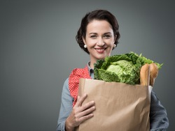 Smiling vintage woman in apron holding a shopping grocery bag.