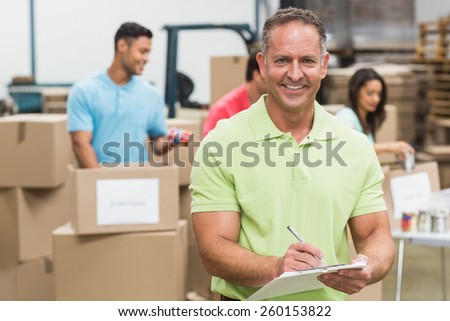 Smiling volunteer man taking notes holding clipboard in a large warehouse