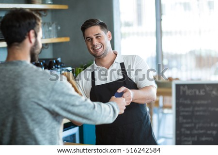 Smiling waiter giving bread to customer at counter in cafe