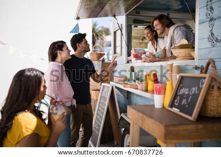 Smiling waiter taking order from couple at counter