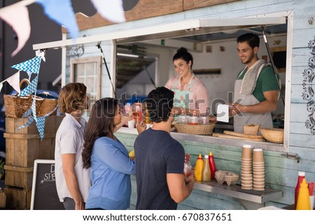 Smiling waiter taking order from customer at counter