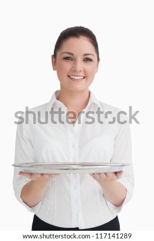 Smiling waitress holding silver tray with two hands