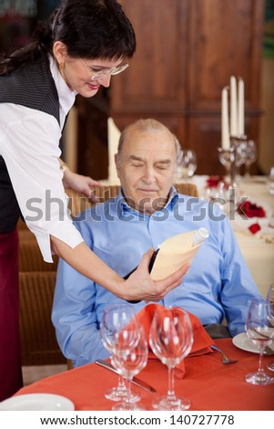 smiling waitress presenting a bottle of wine to elderly guest