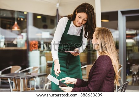 Smiling waitress taking an order in cafe