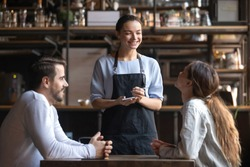 Smiling waitress wear apron hold notepad pen take order talk to clients serving restaurant guests couple choosing food drinks menu sit at cafe coffeehouse table, waiting staff, good customer service