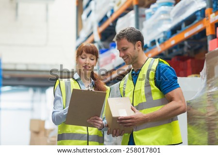 Smiling warehouse manager and delivery man in warehouse