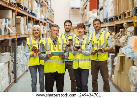 Smiling warehouse team looking at camera in a large warehouse #249434701