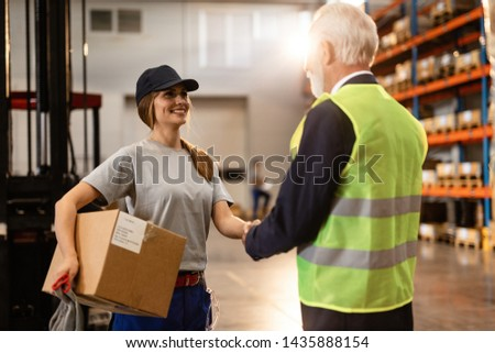 Smiling warehouse worker handshaking with mature businessman while meeting him in industrial building.