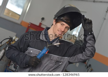 Smiling welder in gray workwear and helmet at work place