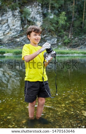 Smiling white boy is washing digital camera in river, it is covered by foam, boy's legs are parlty in water. #1470163646