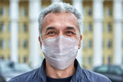 Smiling white caucasian man in a disposable protective surgical mask in a period of coronavirus covid-19 pandemic is walking on the street.