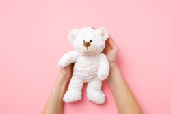 Smiling white teddy bear in girl hands on pastel pink background. Kids best friend. Point of view shot.