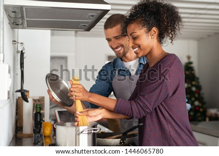 Smiling woman adding pasta to the pot while man holding lid. Happy couple adding spaghetti to boiling water while preparing tasty Italian cuisine. Cheerful couple preparing pasta in pot for dinner.