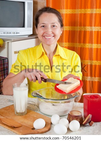 Smiling woman adds margarine into dough in kitchen