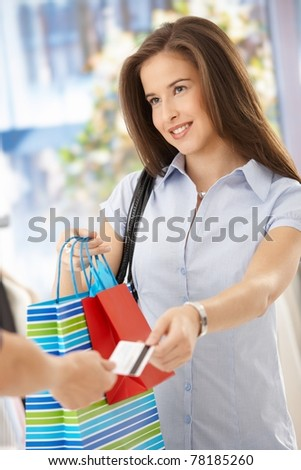 Smiling woman after shopping, taking shopping bags and credit card.?