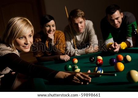 Smiling woman aiming at white ball with cue leaning on snooker table, friends watching.?