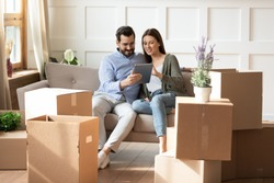 Smiling woman and man using computer tablet together, looking at screen, sitting on couch in living room with cardboard boxes with belongings, choosing moving service for relocation into new house