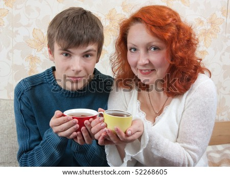 smiling woman and teen boy have tea on sofa at home