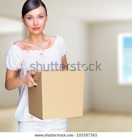 Smiling woman at her home holding boxes. She is Moving at her new home. Mortgage concept