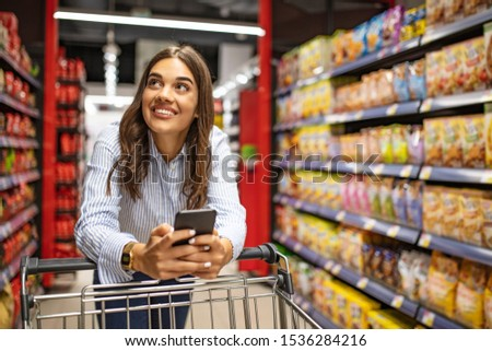 Smiling woman at supermarket. Happy woman at supermarket. Beautiful young woman shopping in a grocery store/supermarket. Shopaholic woman enjoying shopping spree in supermarket