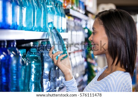 Smiling woman buying a bottle of water in grocery section of supermarket