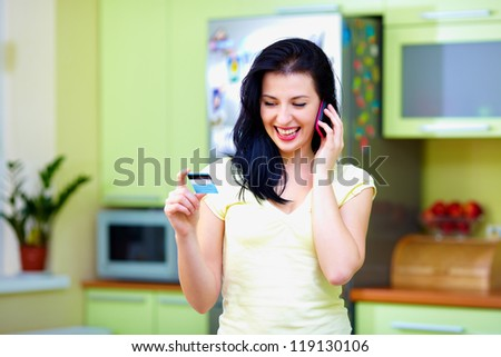 smiling woman calling by phone and holdind credit card, home interior