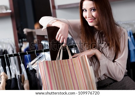 Smiling woman carries paper bags at the store
