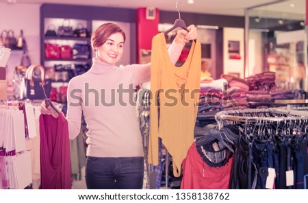 Smiling woman chooses blouses and jackets in the store
