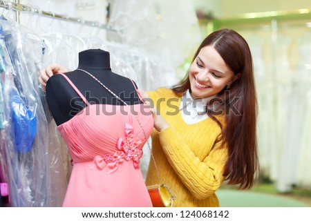 Smiling woman chooses evening gown at clothing store