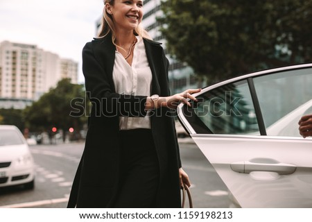 Smiling woman commuter getting out of a taxi. Businesswoman getting off a cab.