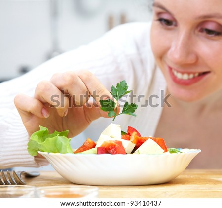 Smiling woman cooking vegetables at kitchen